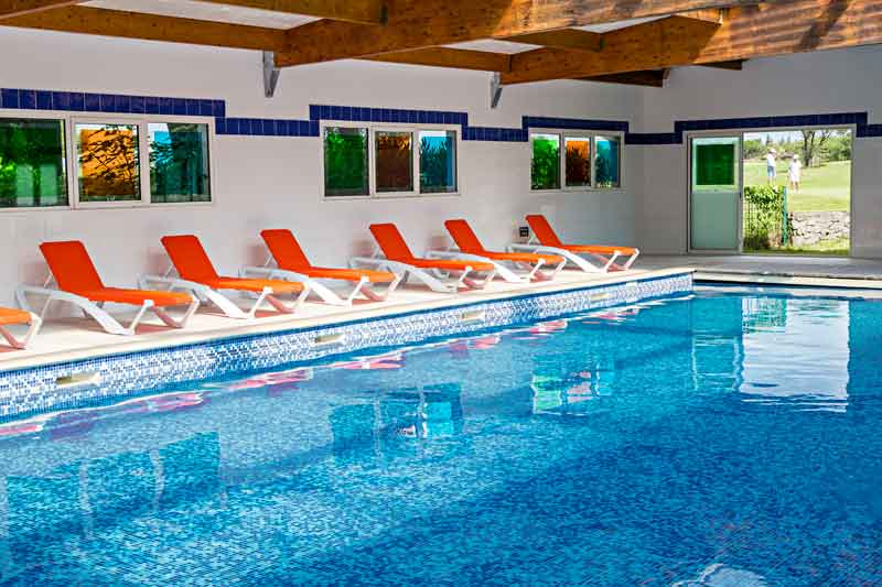 Indoor pool with solarium at the Palmyra Golf hotel and spa in the Occitanie region