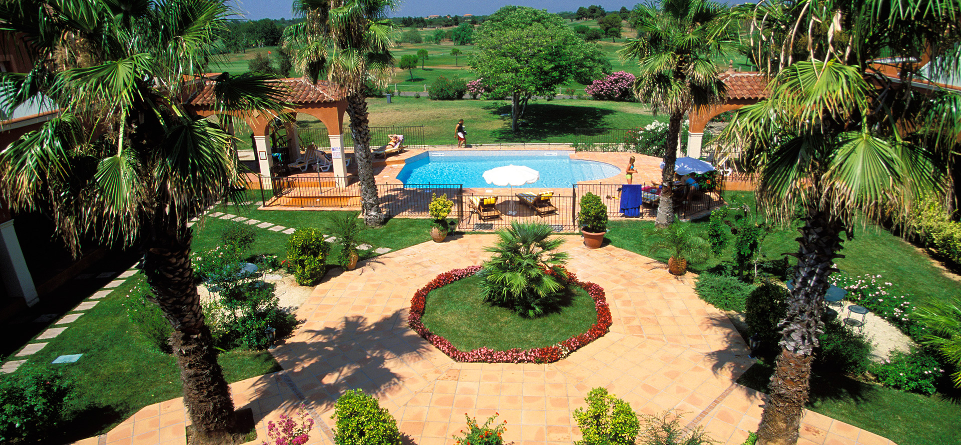 Garden with outdoor pool at the Palmyra Golf hotel in Cap d'Agde